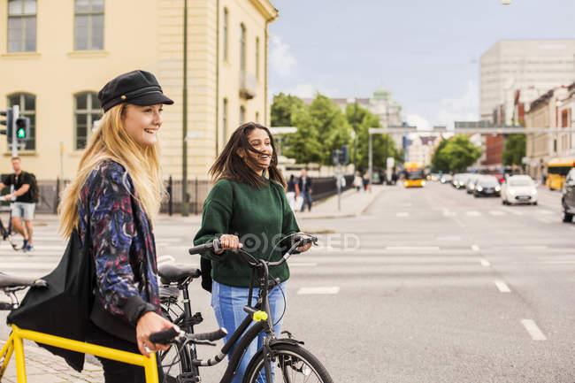 Donne che spingono biciclette in città — Foto stock