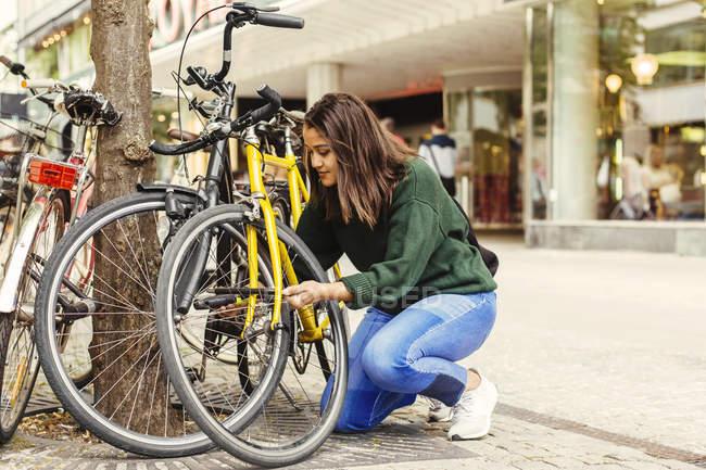 Giovane donna bloccaggio bicicletta — Foto stock