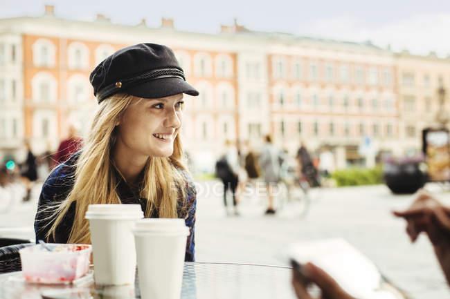 Улыбающаяся молодая женщина сидит в кафе — стоковое фото