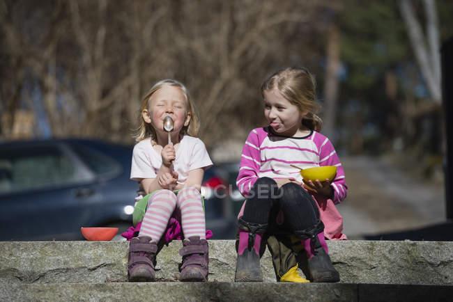 Девушки сидят на стене — стоковое фото