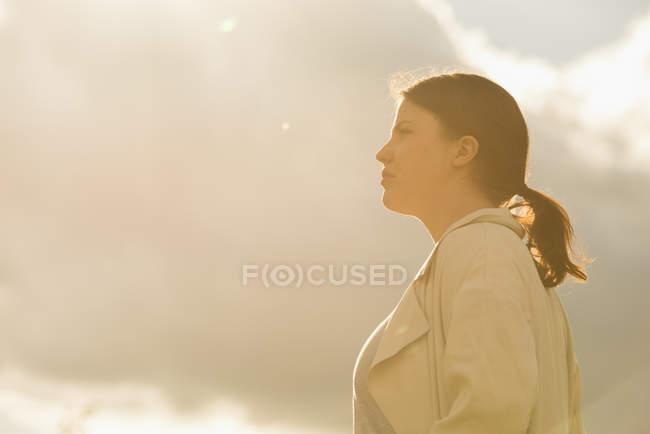 Vista lateral da mulher em pé contra o céu em luz suave — Fotografia de Stock