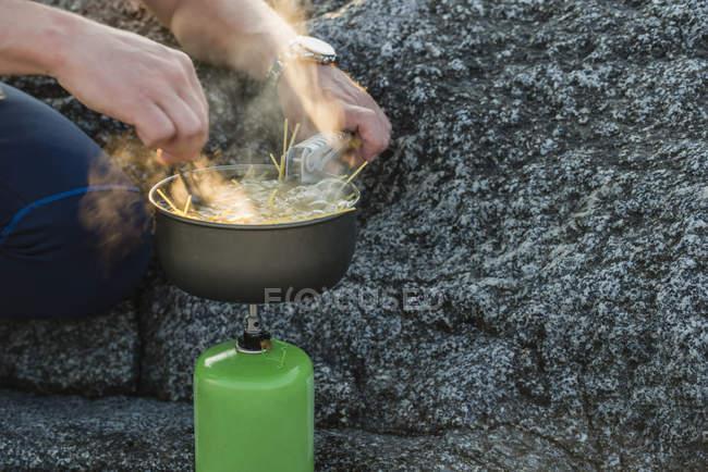 Человек готовит еду на печи для кемпинга — стоковое фото