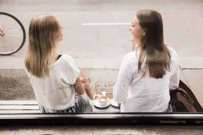 Women talking outside of cafe — Stock Photo