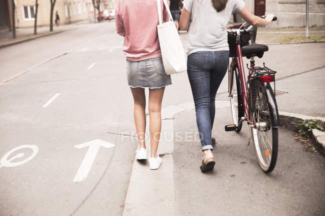 Donne che camminano con la bicicletta — Foto stock