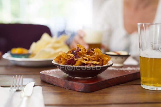 Chips und Bier auf Tisch — Stockfoto