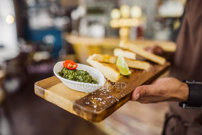 Waiter serving bread with pesto sauce — Stock Photo