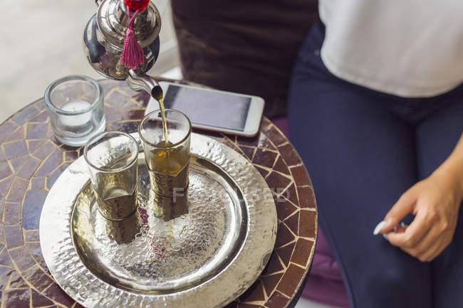 Woman pouring tea into glass — Stock Photo