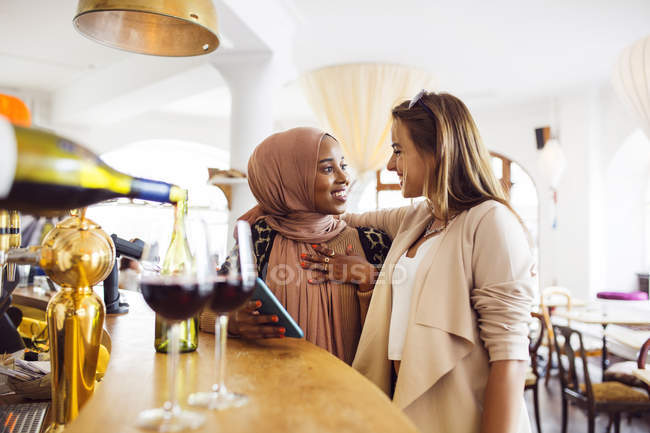 Femmes souriant par comptoir de bar — Photo de stock
