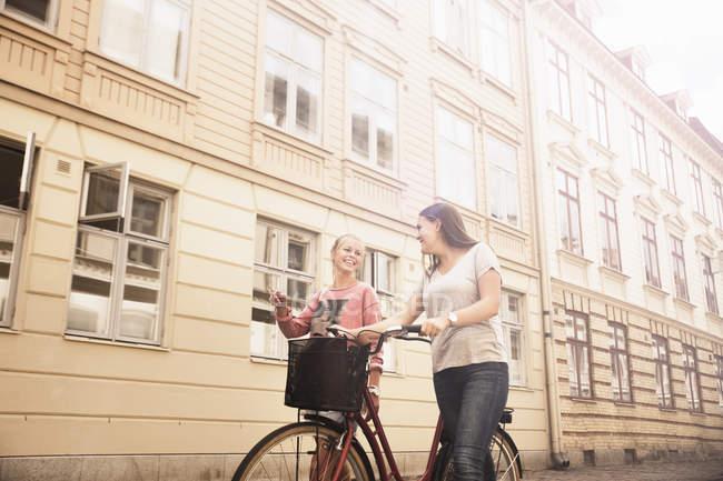 Giovani donne a piedi con la bicicletta — Foto stock