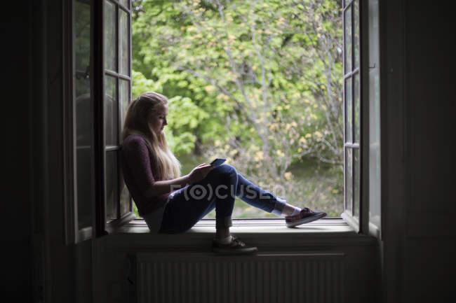 Studentin sitzt mit digitalem Tablet auf Fensterbank — Stockfoto