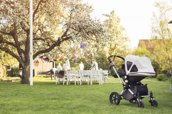 Baby carriage in garden with people in the background — Stock Photo