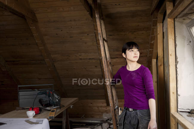 Woman standing in old attic — Stock Photo