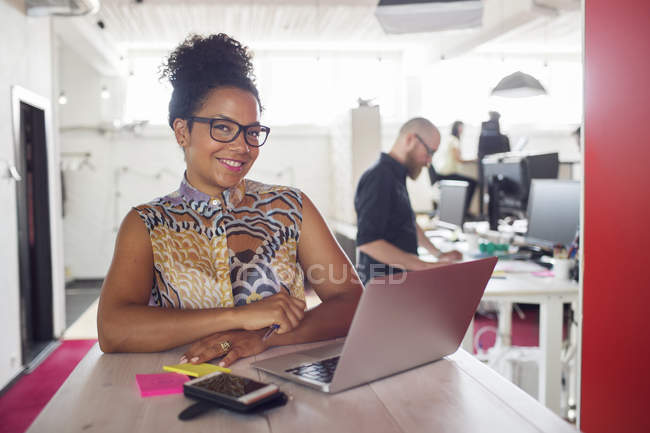 Woman looking in camera while using laptop — Stock Photo