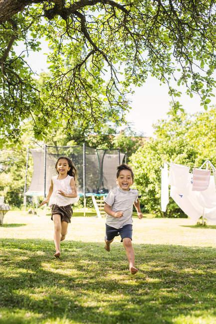 Children running in green yard — Stock Photo