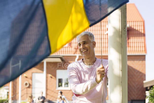 Uomo maturo alzando bandiera svedese nel cortile sul retro — Foto stock