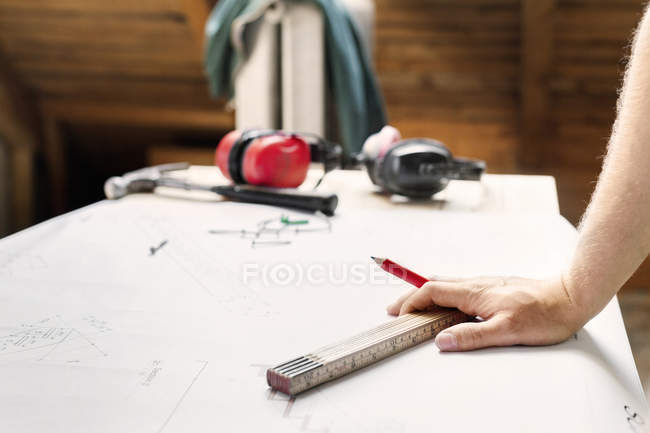 Male hand with tool and pencil — Stock Photo