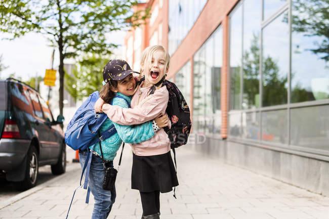 Two girls hugging on street — Stock Photo
