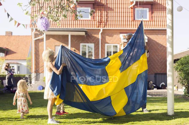 Padre con le figlie che tiene bandierina svedese — Foto stock