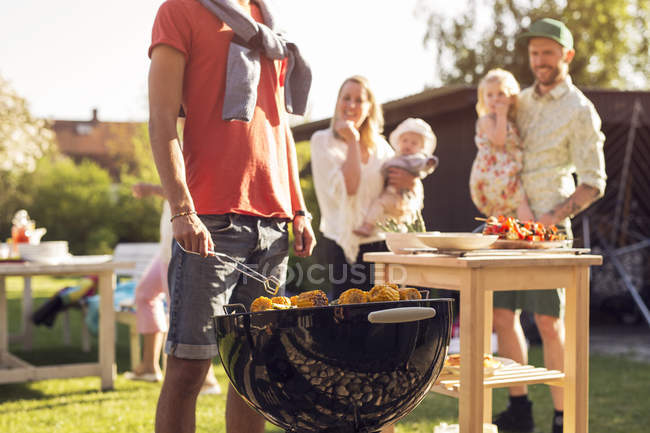 Family with children watching man at barbecue grill — Stock Photo