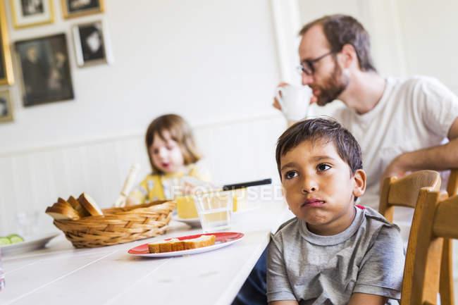 Familia sentada en la mesa de la cena - foto de stock