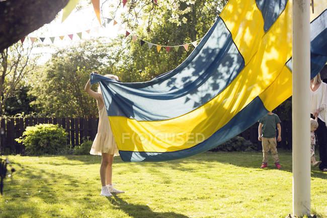 Девочка держит шведский флаг с семьей в саду — стоковое фото