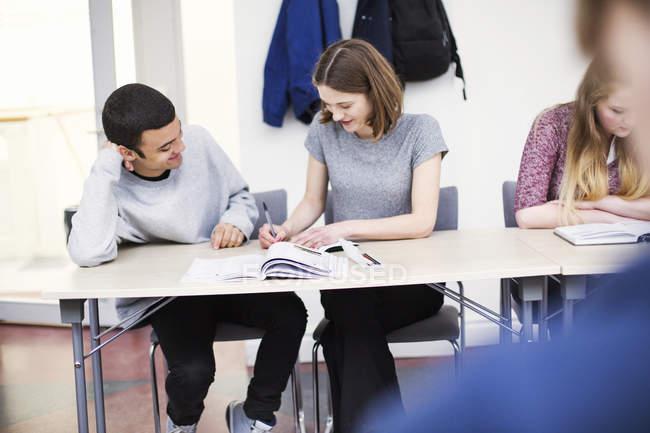 Studenti seduti in aula e la scrittura nei taccuini — Foto stock