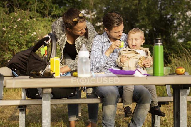 Family sitting by picnic table — Stock Photo