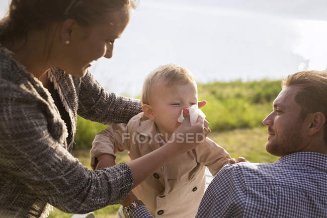 Mother helping son blowing nose — Stock Photo