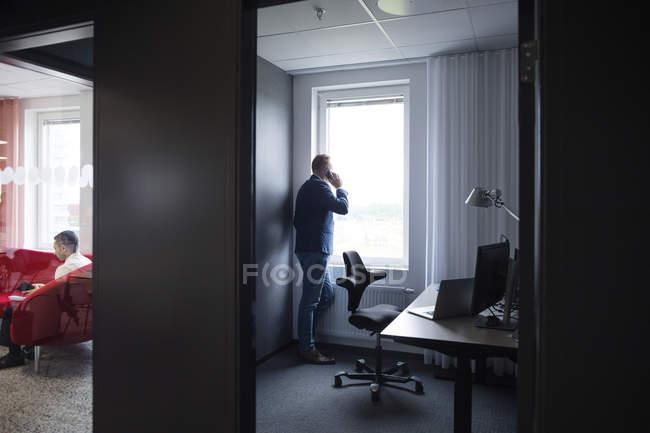 Mann am Smartphone im Büro sprechen — Stockfoto