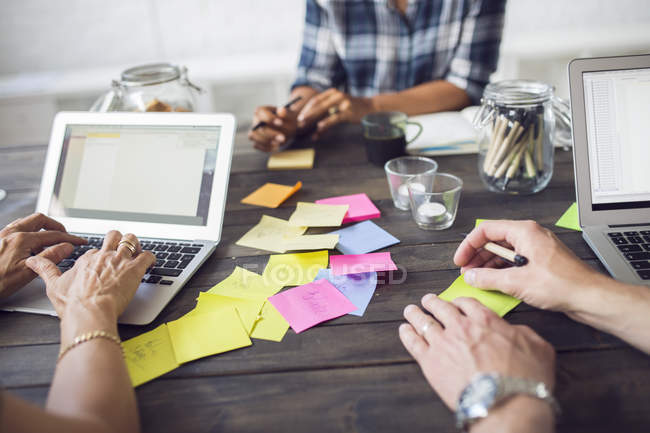 Mitarbeiter, die mit Laptops und Post-it-Notizen arbeiten — Stockfoto