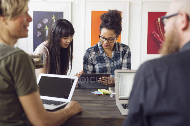 Coworkers sitting at table with laptops — Stock Photo
