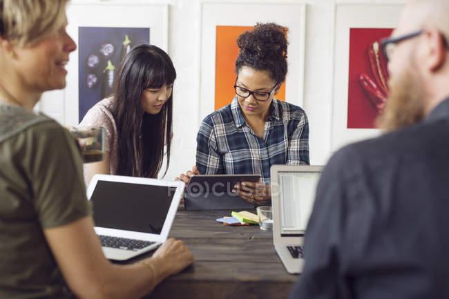 Compañeros de trabajo sentado en mesa con ordenadores portátiles - foto de stock