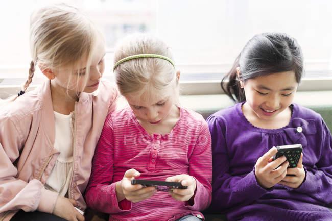 Три девушки сидят со смартфонами — стоковое фото