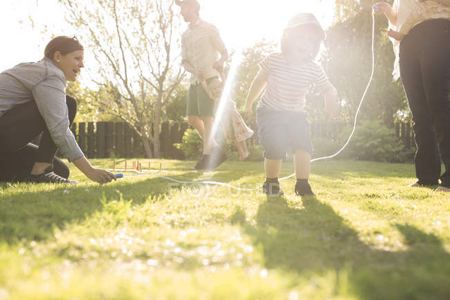 Girl skipping rope in garden with parents — Stock Photo