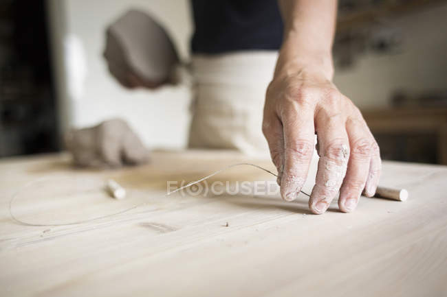 Female potter working with wire — Stock Photo