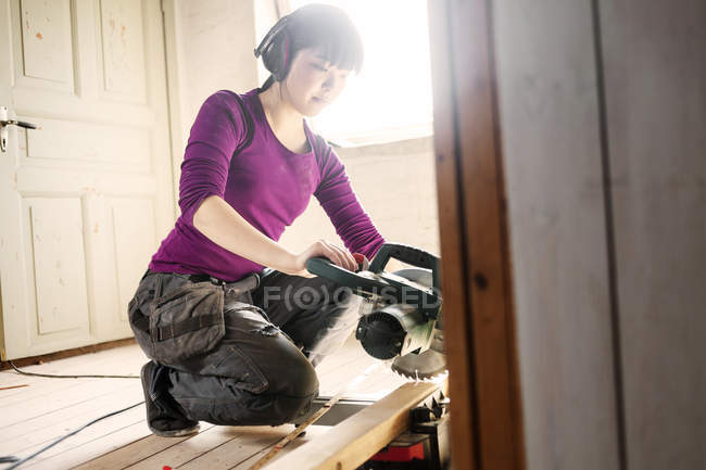 Woman working with wood and circular saw — Stock Photo