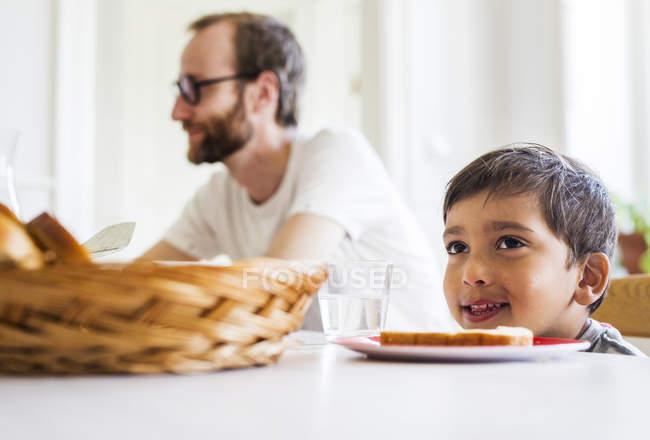 Niño sentado en la mesa de la cena - foto de stock