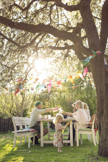 Family sitting at dinner table at garden party in back yard — Stock Photo