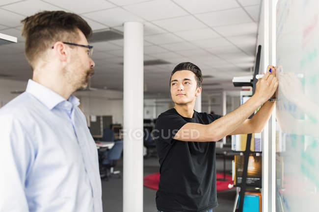 Kolleginnen und Kollegen neben Whiteboard im Büro stehen und sahen einander — Stockfoto