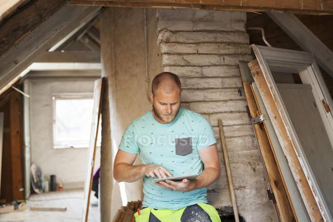 Человек работает над ремонтом старого чердака — стоковое фото