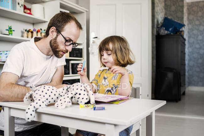 Mann-Lesebuch mit Mädchen — Stockfoto