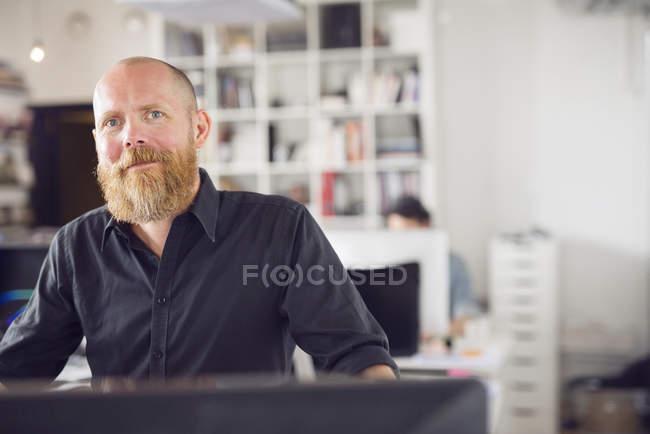 Человек, глядя в камеру в офисе — стоковое фото