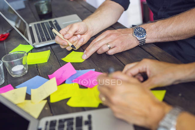 Coworkers writing on post-it notes — Stock Photo