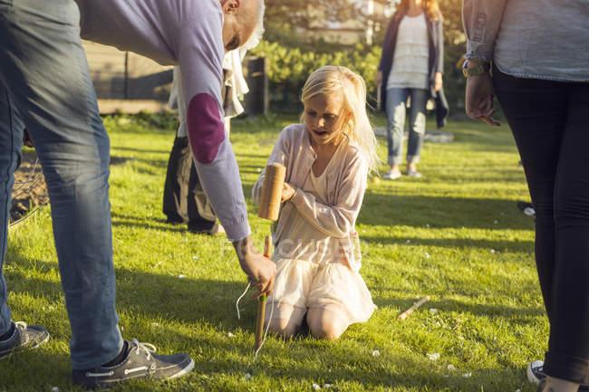Девушка молотит кол в саду с дедушкой — стоковое фото