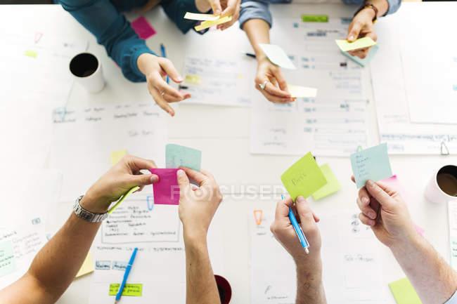 Vista dall'alto dei colleghi che utilizzano note adesive durante la riunione di lavoro — Foto stock