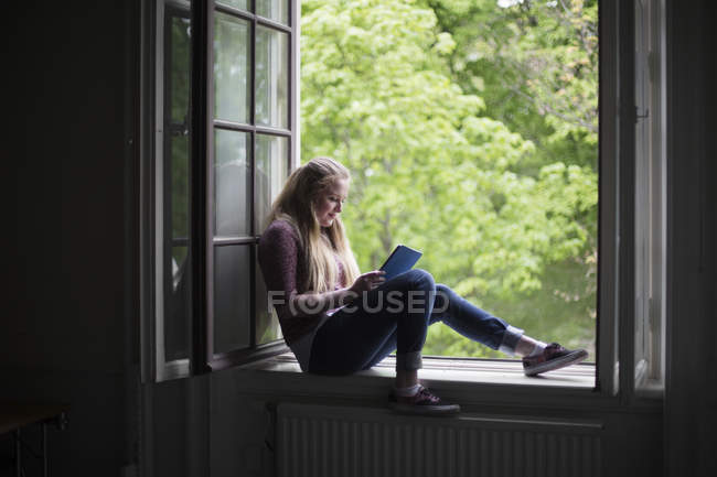 Female student sitting on window sill with digital tablet — Stock Photo