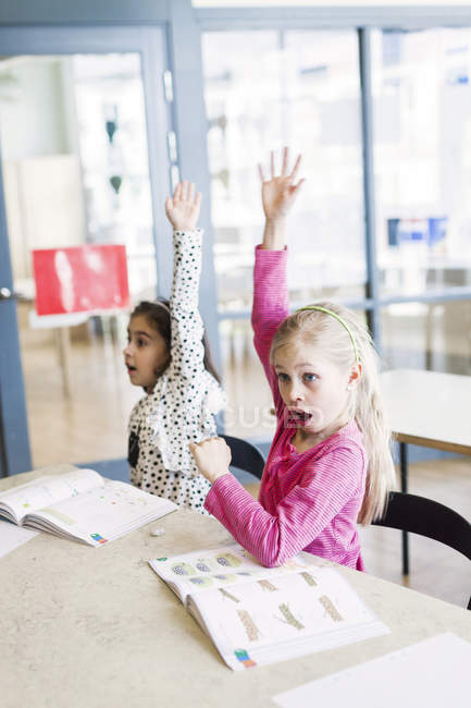 Girls rising hands in classroom — Stock Photo