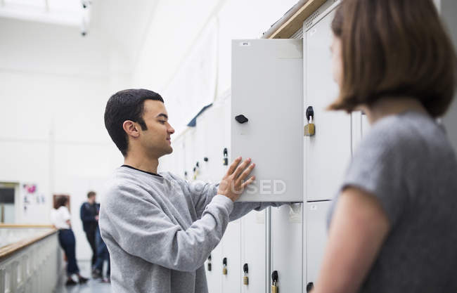 Two students talking in front of open locker with unrecognizable people in background — Stock Photo