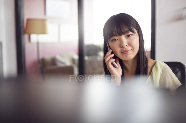 Woman using phone in office — Stock Photo