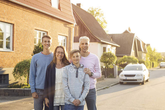 Family with two sons posing on street — Stock Photo